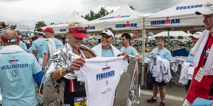 An Ironman holds up her finisher gear